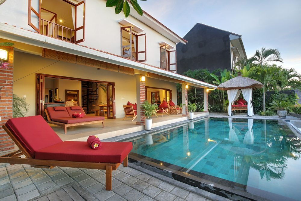 The villa pool  with red sundeck and small gazebo