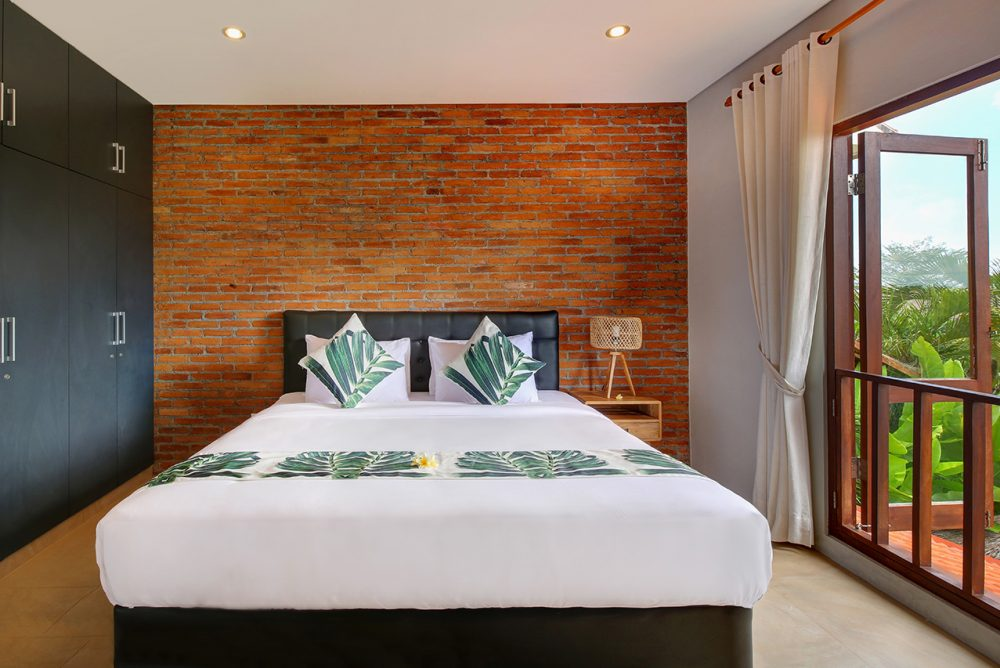 double bed at villa subak with traditional brick as the background