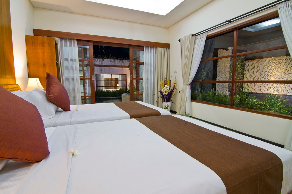 twin bedroom at villa maha with minimalist design - facing to the pool and garden
